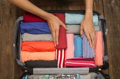 woman-packing-luggage-new-journey-260nw-514740439