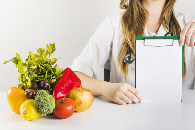 female-dietician-s-hand-holding-blank-clipboard-with-healthy-food-desk_23-2147882168